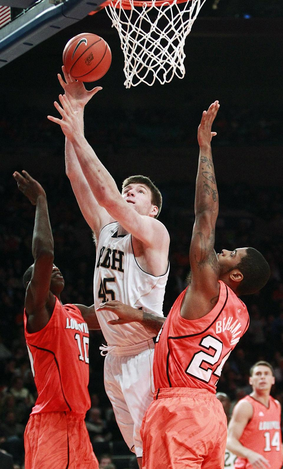 Notre Dame's Jack Cooley (45) drives past Louisville's Gorgui Dieng (10) and Chane Behanan (24) during the first half of an NCAA college basketball game in the semifinals of the Big East Conference tournament in New York, Friday, March 9, 2012. (AP Photo/Frank Franklin II)