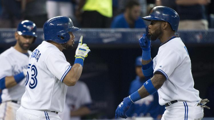 Toronto Blue Jays shortstop Jose Reyes, right, celebrates his solo home run with teammate Melky Cabrera, left, while playing against the Boston Red Sox during the sixth inning of a baseball game, Tuesday, July 22, 2014 in Toronto. (AP Photo/The Canadian Press, Nathan Denette)