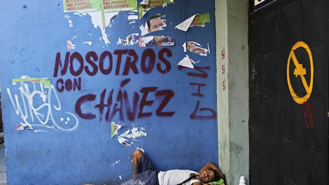 """Homeless Efrain Juanipas, 37, rests on a makeshift bed made from a  a cardboard box next to graffiti that reads in English: """"We're with Chavez,"""" in reference to Venezuela's President Hugo Chavez, in Caracas, Venezuela, Monday, Oct. 8, 2012. Chavez won re-election and a new endorsement of his socialist project Sunday, surviving his closest race yet after a bitter campaign against opposition candidate Henrique Capriles.(AP Photo/Rodrigo Abd)"""