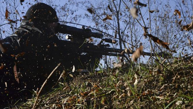In this photo taken on Friday, Nov. 21, 2014, a Pro-Russian rebel fires sniper rifle toward Ukrainian army positions at the frontline near Peski village, Donetsk, Eastern Ukaine. U.S. Vice President Joe Biden criticized Russia on Friday for its role in eastern Ukraine, urging Moscow to uphold a cease-fire in the war-torn region as he visited Kiev on the anniversary of the country's anti-government protests. (AP Photo/Mstyslav Chernov)