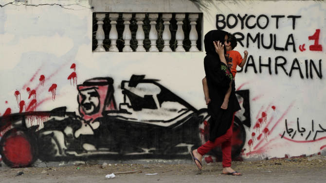 """A Bahraini carrying a child passes a wall Thursday, April 5, 2012, in Barbar, Bahrain, west of the capital of Manama, that is painted with graffiti depicting Bahrain's King Hamad bin Isa Al Khalifa in a race car, calling for a boycott of this year's Formula One Bahrain grand prix, scheduled for April 22. The Arabic is a signature reading """"free men of Barbar."""" A year after an anti-government uprising forced Bahrain's rulers to cancel the kingdom's coveted Formula One race, the grand prix is again smack in the middle of a power struggle. (AP Photo/Hasan Jamali)"""