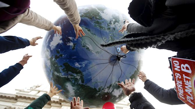 Protesters throw up a globe-shaped balloon during a rally held the day before the start of the 2015 Paris World Climate Change Conference, known as the COP21 summit, in Rome