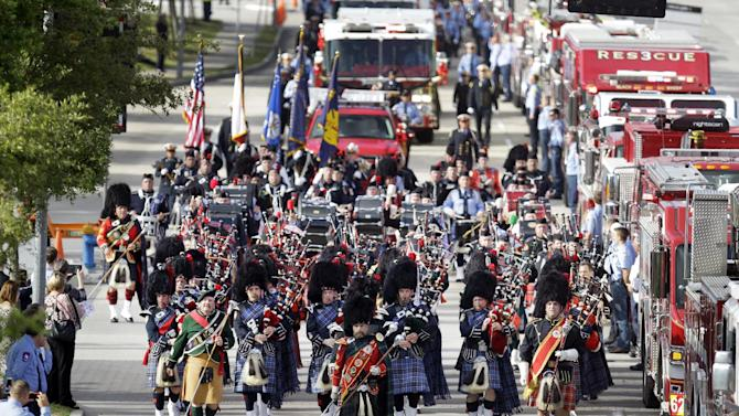 Bagpipers lead firefighters and others in march to a memorial service honoring four Houston firefighters at Reliant Stadium, Wednesday, June 5, 2013 in Houston. Dozens of fire trucks and emergency services vehicles from New Orleans, Dallas and elsewhere formed a long procession on flag-lined streets leading to the stadium. Killed in the fire when the motel structure collapsed were Capt. Matthew Renaud, 35, engineer operator Robert Bebee, 41, firefighter Robert Garner, 29, and Anne Sullivan, 24, a probationary firefighter who had graduated in April from the Houston Fire Department Academy. (AP Photo/Houston Chronicle, Melissa Phillip) MANDATORY CREDIT