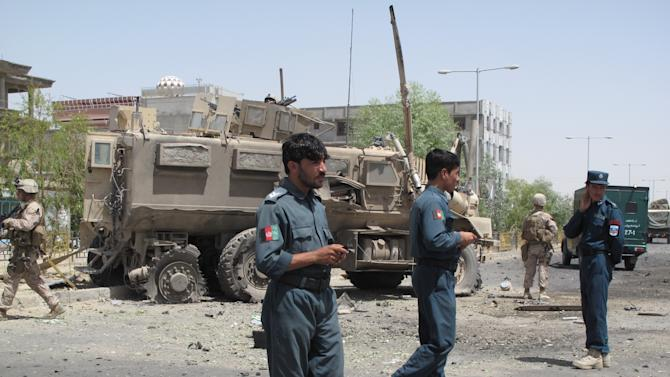 Afghan policemen investigate the site of a suicide attack in the provincial capital city of Laskar-Gah, Helmand Province, southern Afghanistan, Wednesday, Aug, 28, 2013. A suicide attack against a coalition convoy and a separate rocket attack against tankers carrying fuel for NATO on Wednesday killed many civilians and wounded tens of people in southern and western Afghanistan, officials said. (AP Photo/Abdul Khaleq)