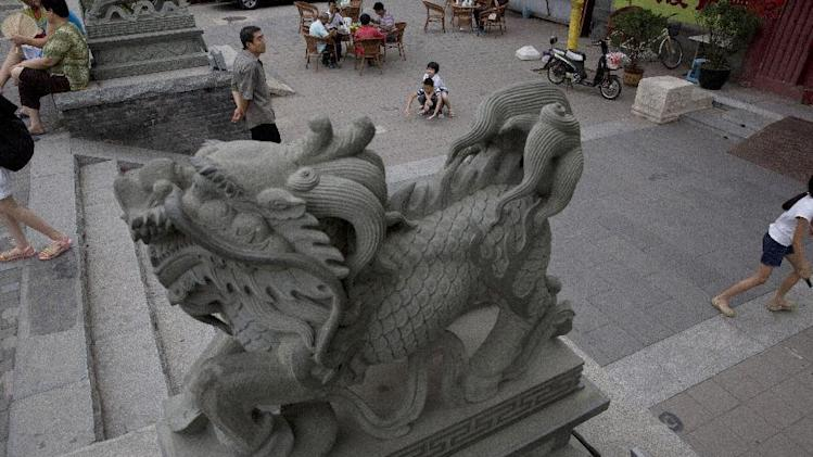 Residents mingle outside a temple in an area popular with tourists for its local flavor in Beijing, China, Friday, Aug. 22, 2014. Increasingly Beijing's old districts are undergoing modernization that some critics say deprives the city of its charm.(AP Photo/Ng Han Guan)