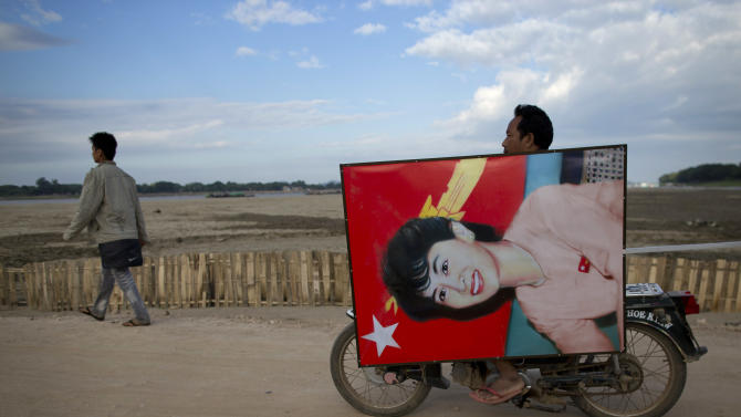 A supporter of opposition leader Aung San Suu Kyi rides a motor bike transporting a portrait of her for a public rally close to Letpadaung mine in Monywa, northwestern Myanmar, Friday, Nov 30, 2012.  Opposition leader Aung San Suu Kyi has publicly criticized the forcible crackdown on protesters at a mine in northwestern Myanmar, saying the public needs an explanation of the violence that injured dozens, including Buddhist monks.   (AP Photo/Gemunu Amarasinghe)