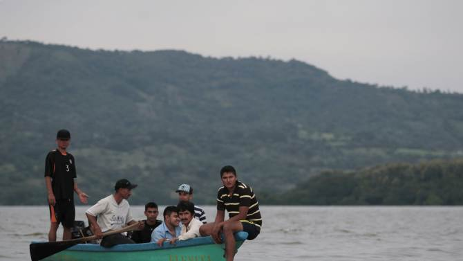 Local residents involved in a search operation sit in a boat after a Salvadoran Air Force plane crashed in Suchitlan Lake