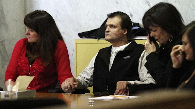 William Coultas, second from left, holds hands with his wife, Chris Coultas,  as Christine Schwanenberg, second from right, and his daughter, Ricci Coultas, react after a verdict is reached regarding a 2008 helicopter crash that killed 8 firefighters and the pilot in Portland, Ore., Tuesday, March 27, 2012.  Coultas is the surviving co-pilot while Schwanenberg's husband, who was the pilot, was killed.  The jury ruled that a problem with an engine was responsible for the crash in Northern California. and awarded a verdict against General Electric for $177 million.  At left is Coultas' wife, Chris Coultas and at right is his daughter, Ricci Coultas.(AP Photo/Don Ryan)
