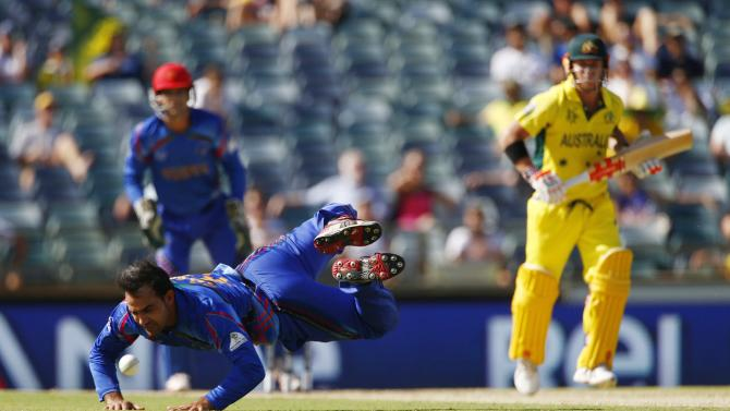 Afghanistan's bowler Shinwari dives for the ball off Australian batsman Warner, as wicketkeeper Zazai watches on, during their Cricket World Cup match in Perth