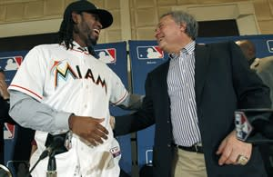 FILE - In this Dec. 7, 2011, file photo, Miami Marlins owner Jeffrey Loria, right, and newly signed free-agent shortstop Jose Reyes interact after a news conference at Major League Baseball's winter meetings in Dallas. The Marlins' latest payroll purge received final approval Monday, Nov. 19, 2012, from Commissioner Bud Selig's office. In a conference call, team president of baseball operations Larry Beinfest confirmed the trade was necessary because Loria wanted to pare payroll. Reyes, who is due a guaranteed salary of $96 million, was traded to the Toronto Blue Jays. (AP Photo/LM Otero, File)