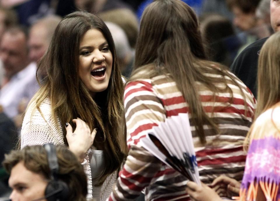 Khloe Kardashian, wife of Dallas Mavericks forward Lamar Odom, talks with fans as she makes her way to her seat in the stands before an NBA basketball game against the Utah Jazz, Saturday, March 3, 2012, in Dallas. (AP Photo/LM Otero)