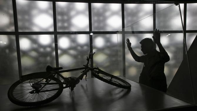 A man looks at a tsunami-damaged bike found in the ruins of a house, now displayed at Aceh Tsunami Museum in Banda Aceh