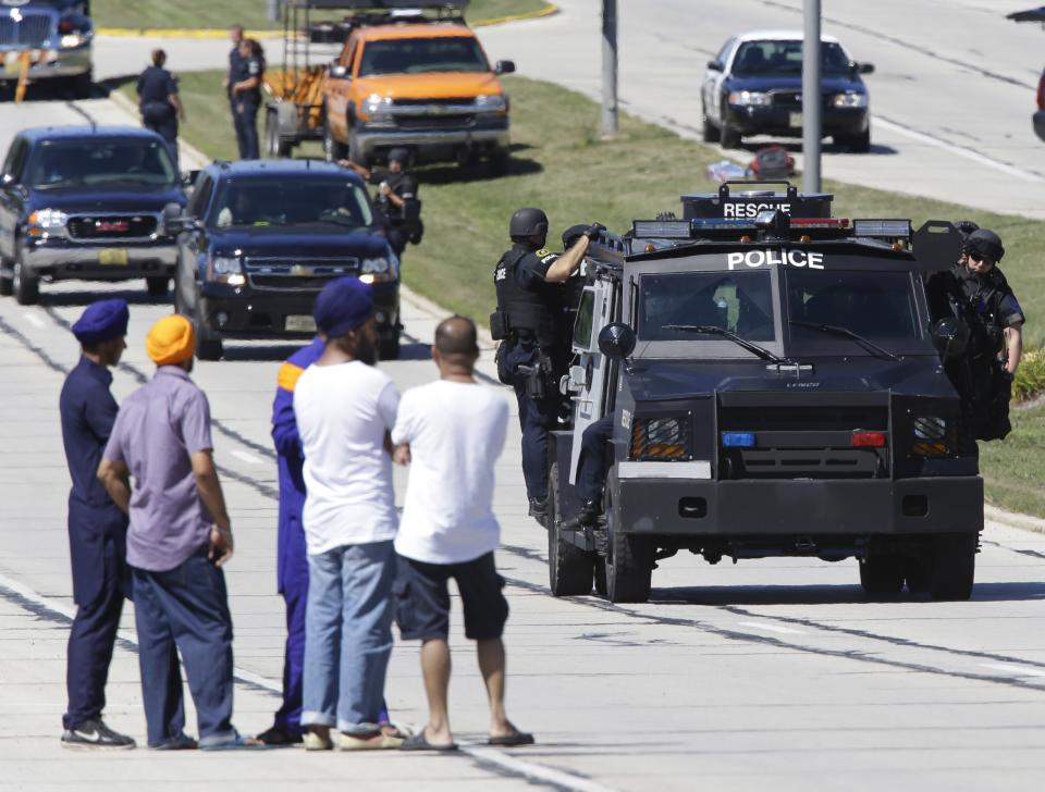 People watch police personnel outside the Sikh Temple in Oak Creek, Wis., where a shooting took place Sunday, Aug 5, 2012. (AP Photo/Jeffrey Phelps)
