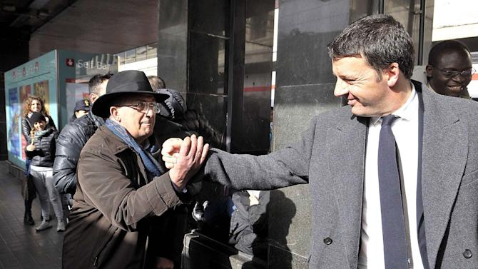CORRECTS DATE -- Democratic Party secretary Matteo Renzi is greeted by a passer-by as he arrives at Rome's main train station, Monday, Feb. 17, 2014. Italian President Giorgio Napolitano asked the brash young leader of the Democratic Party to try to form a new government after he managed to oust the previous premier in a power grab. Renzi, the 39-year-old mayor of Florence, met for more than an hour with President Napolitano. Afterward he said he would go to work immediately on forging a new coalition, with talks with potential partners formally beginning on Tuesday. (AP Photo/Sub) ITALY OUT