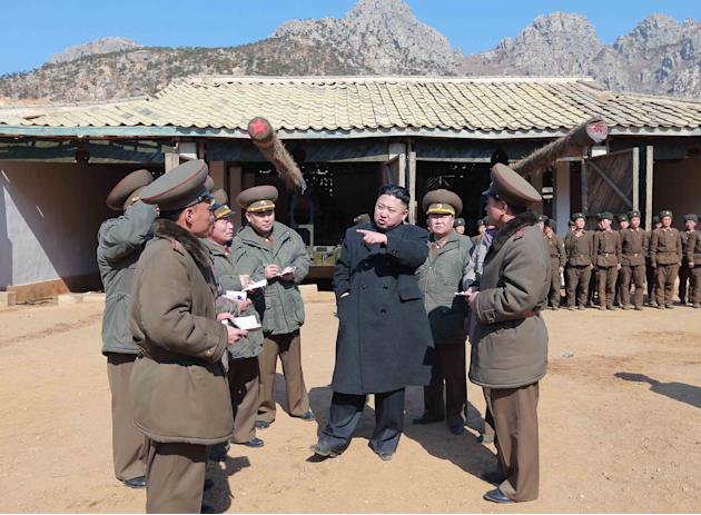 In this March 11, 2013 photo released by the Korean Central News Agency (KCNA) and distributed March 12, 2013 by the Korea News Service, North Korean leader Kim Jong Un, center, confers with military