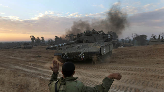 An Israeli soldier guides a tank to a new position at a staging area near the Israel Gaza Strip Border, southern Israel, Thursday, Nov. 22, 2012. A cease-fire agreement between Israel and the Gaza Strip's Hamas rulers took effect Wednesday night, bringing an end to eight days of the fiercest fighting in years and possibly signaling a new era of relations between the bitter enemies. (AP Photo/Lefteris Pitarakis)