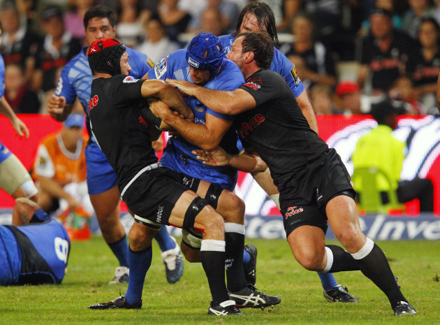Coastal Sharks' Jacques Botes (L) and Bismarck du Plessis (R) tackle Western Force's Nathan Sharpe during the Super 15 Rugby Union match between Western Force of Australia and Coastal Sharks from Durb