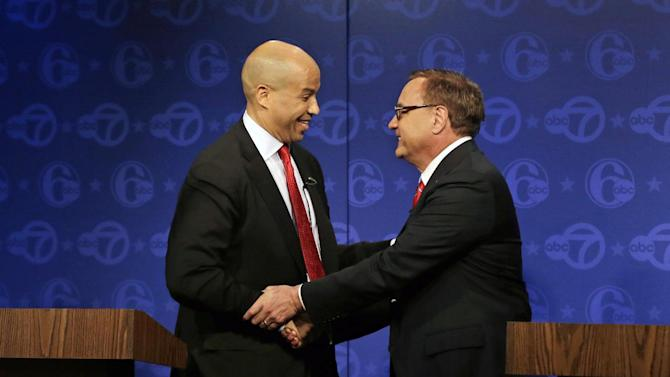 Democratic Newark Mayor Cory Booker, left, and Republican Steve Lonegan shake hands after their first debate in the U.S. Senate campaign on Friday, Oct. 4, 2013, in Trenton, N.J. The two squared off in the first debate of the campaign with just 12 days to go before the special Senate election. (AP Photo/Mel Evans)