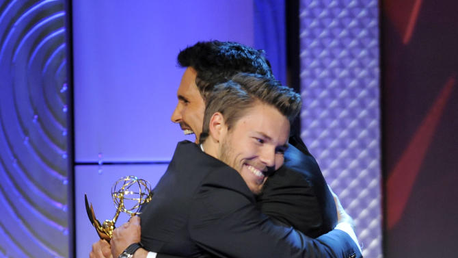 """Scott Clifton, left, from the cast of """"The Bold and the Beautiful,"""" is congratulated by Don Diamont, after Clifton won the award for outstanding supporting actor in a drama series at the 40th Annual Daytime Emmy Awards on Sunday, June 16, 2013, in Beverly Hills, Calif. Don Diamont presented the award. (Photo by Chris Pizzello/Invision/AP)"""