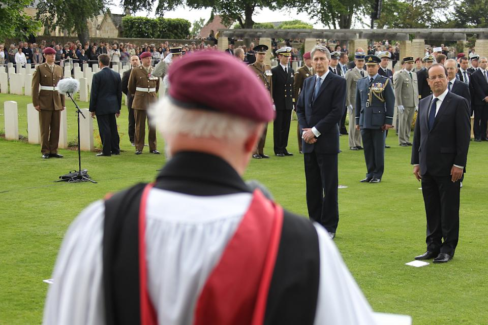 British minister of Defense Philippe Hammond, rear left and French President Francois Hollande, center, attends at the ceremony commemorating the 68th anniversary of the D-Day invasion of France began in 1944, in the British war cemetery of Ranville, western France, Wednesday, June 6, 2012. (AP Photo/David Vincent, Pool)