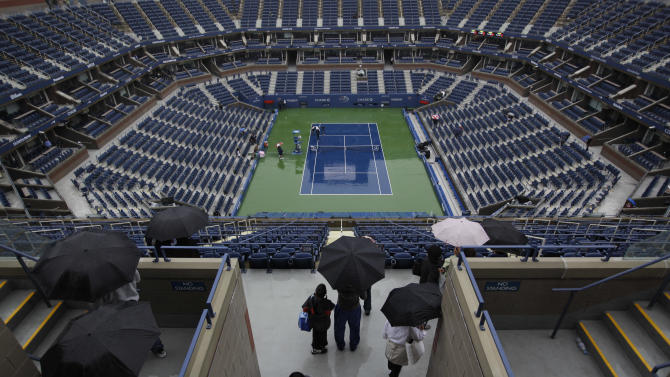 Fans arrive at Arthur Ashe Stadium during the U.S. Open tennis tournament in New York, Wednesday, Sept. 7, 2011. Because of rain, Wednesday's play at the U.S. Open will not start before noon. (AP Photo/Matt Slocum)
