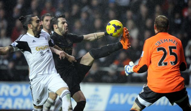 Swansea City's Chico Flores challenges Manchester City's Alvaro Negredo during their English Premier League soccer match at the Liberty Stadium in Swansea