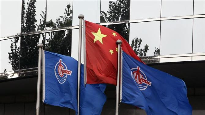 File photo of flags of China National Offshore Oil Corp (CNOOC) flying beside the China flag in front of its headquarters building in Beijing