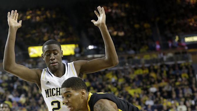 Iowa forward Roy Devyn Marble drives on Michigan guard Caris LeVert (23) during the first half of an NCAA college basketball game at Crisler Arena in Ann Arbor, Mich., Sunday, Jan. 6, 2013. (AP Photo/Carlos Osorio)