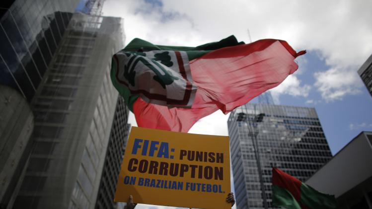 Soccer fan holds a banner next to a flag of Brazil's Portuguesa soccer club during a protest against corruption in the football in Sao Paulo