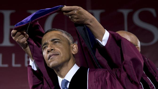 President Barack Obama receives an honorary degree from Robert Davidson, Chair of the Board of Trustees, partially visible, during the Morehouse College 129th Commencement ceremony, Sunday, May 19, 2013, in Atlanta. Morehouse is the historically black, all-male institution that counts Martin Luther King Jr. among its alumni. It is Obama's second graduation speech of the year. (AP Photo/Carolyn Kaster)