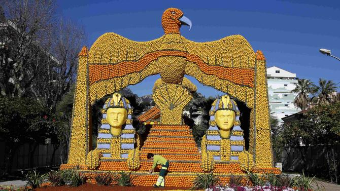 """A worker puts the final touch to a replica of a giant eagle and pharaons made with lemons and oranges which shows a scene of the movie """"Cleopatra"""" during the Lemon festival in Menton"""