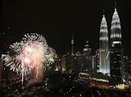 Fireworks light up the sky near the landmark Petronas Twin Towers (R) during new year celebrations in Kuala Lumpur on January 1, 2011. The top 100 fast-globalising companies from rapidly developing economies are outpacing their rivals from developed economies in terms of expansion, job creation and productivity, said the Boston Consulting Group (BCG) study