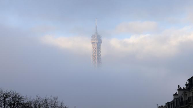 The Eiffel Tower is partially covered by an early morning fog in Paris