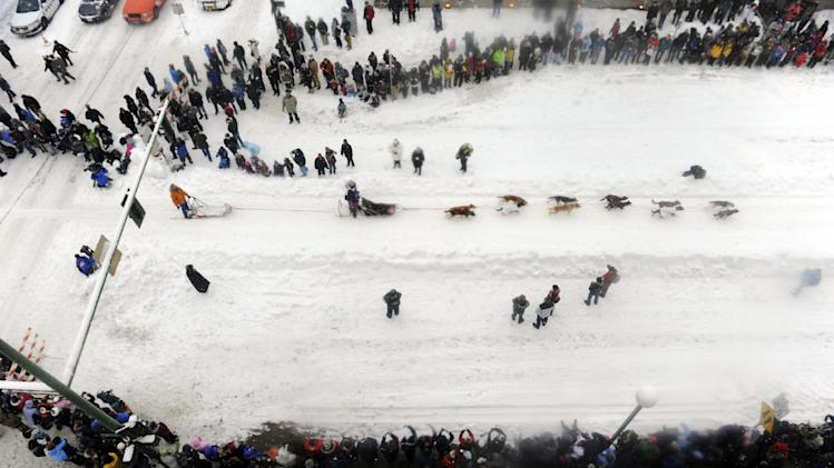 A musher runs its team down 4th Avenue during the ceremonial start of the Iditarod trail sled dog race, Saturday, March 3, 2012, in Anchorage, Alaska. (AP Photo/The Anchorage Daily News, Marc Lester)