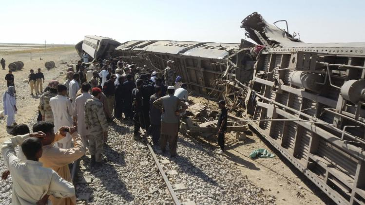 Officials, rescue workers and residents gather near the passenger train derailed after it was hit by a bomb attack in Dera Murad Jamali