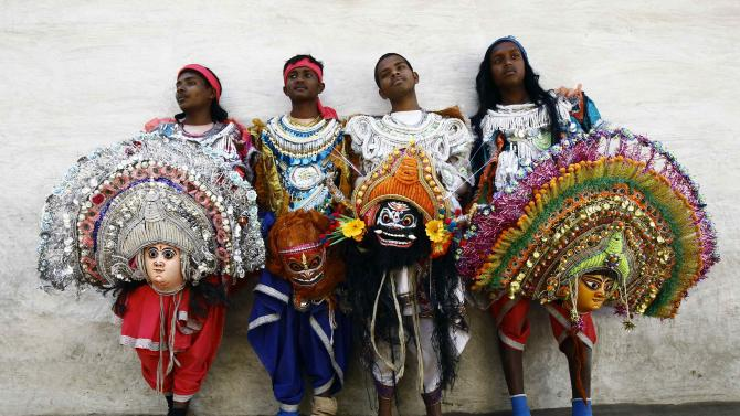 Dancers hold their masks as they pose for pictures after taking part in the day long village festival of Chhau, at Malti village in Purulia