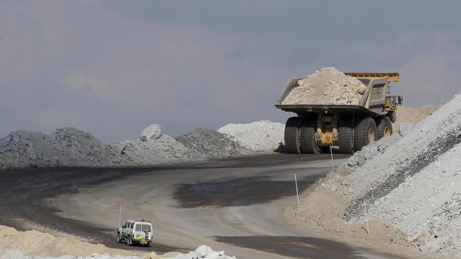 In this Sept. 11, 2012 photo, a four-wheel-drive vehicle follows a large mining truck as it makes its way to the top of a Boggabri coal mine near Gunnedah, Australia, 450 kilometers (280 miles) northwest of Sydney. Soaring coal prices fueled by China's economic growth have made mining parts of the Australian landscape far more lucrative than farming it. (AP Photo/Rob Griffith)