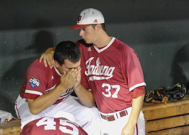 Indiana's Kyle Schwarber, left, is comforted by Scott Effross as they sit in the dugout after losing to Oregon State 1-0 in an NCAA College World Series elimination baseball game in Omaha, Neb., Wedne