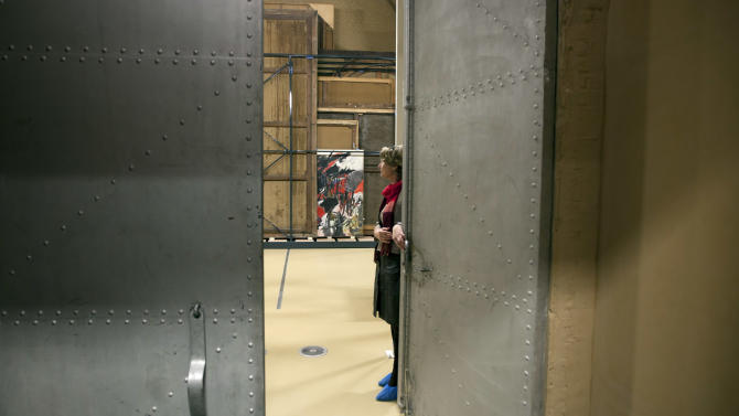 """Press and communications officer Veronique Van Passel opens giant steel doors which lead to an interior warehouse in the Antwerp Royal Museum of Fine Arts in Antwerp, Belgium on Thursday, April 4, 2013. Just as the famous Amsterdam Rijksmuseum in neighbouring Netherlands has returned """"The Night Watch"""" of its most famous painter, Rembrandt van Rijn, back in the main building after a ten-year renovation, Antwerp is hiding five oversized Rubens paintings in a special depot to protect them against the rough and tumble of four more years of works. (AP Photo/Virginia Mayo)"""