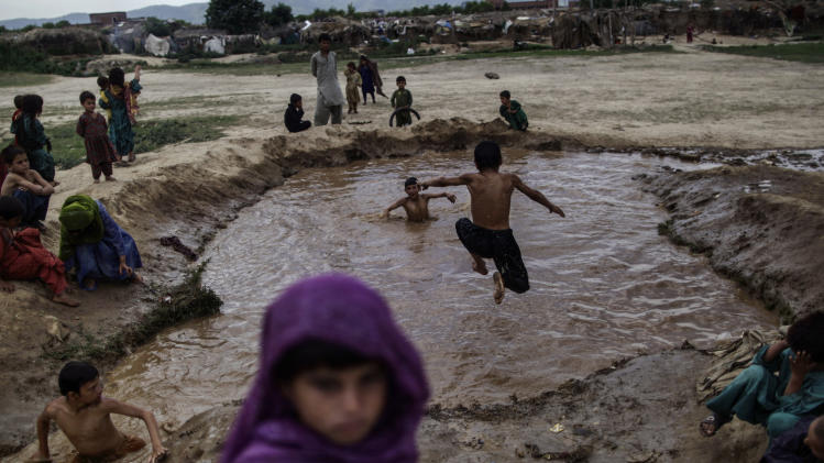 Afghan refugee children, swim in muddy water created from a broken water pipe, on the outskirts of Islamabad, Pakistan, Monday, June 17, 2013. Pakistan hosts over 1.6 million registered Afghans, the largest and most protracted refugee population in the world, according to the U.N. refugee agency. (AP Photo/Muhammed Muheisen)