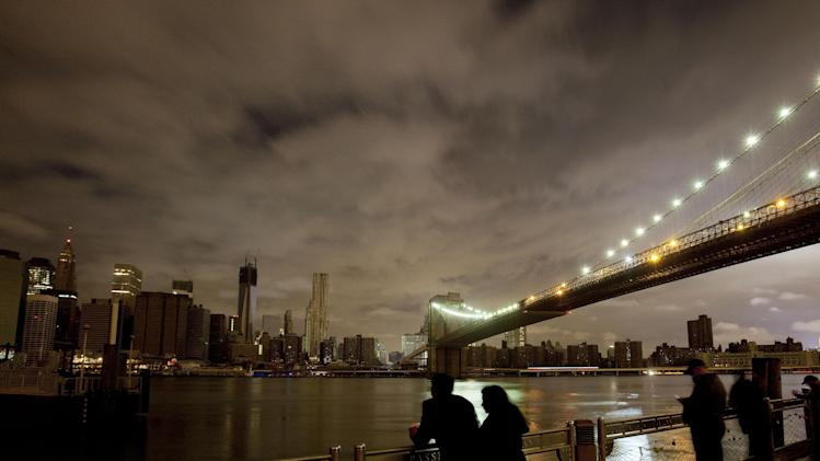 People stop along the Brooklyn waterfront to look at the Brooklyn Bridge and the Manhattan skyline, Tuesday, Oct. 30, 2012 in New York. Much of lower Manhattan is without electric power following the impact of superstorm Sandy. (AP Photo/Mark Lennihan)