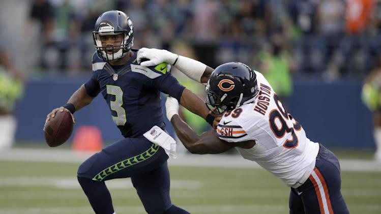 Seattle Seahawks quarterback Russell Wilson (3) tries to escape the grasp of Chicago Bears defensive end Lamarr Houston in the first half of a preseason NFL football game, Friday, Aug. 22, 2014, in Seattle. The Seahawks won 34-6