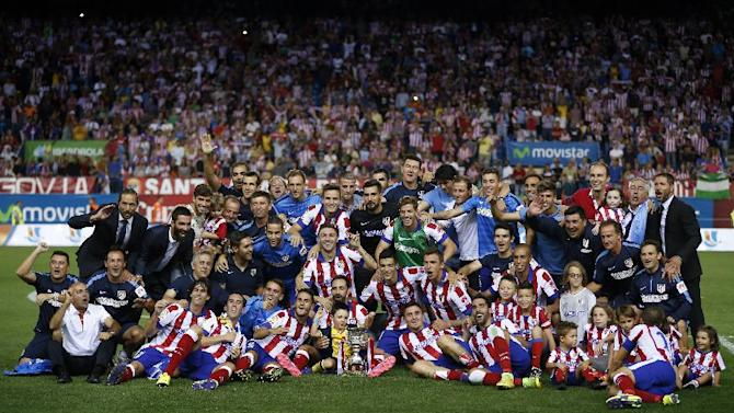 Atletico Madrid players pose with the Spanish Super Cup trophy after defeating Real Madrid on the second round soccer match at the Vicente Calderon stadium in Madrid, Spain, Friday, Aug. 22, 2014