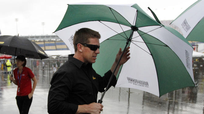 Carl Edwards takes cover under an umbrella as he leaves the drivers' meeting before the NASCAR Sprint Cup auto race at Kentucky Speedway at Sparta, Ky., Saturday, June 29, 2013. (AP Photo/James Crisp)