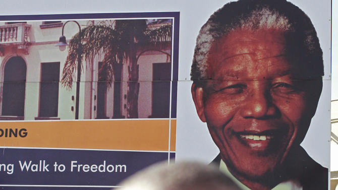 A man passes a advertising board for the Nelson Mandela museum, showing the face of former South African president Nelson Mandela, right rear, in the town of Umtata, South Africa, Friday, June 28, 2013. Members of Nelson Mandela's family as well as South African Cabinet ministers have visited the hospital where the 94-year-old former president is critically ill. (AP Photo/Schalk van Zuydam)