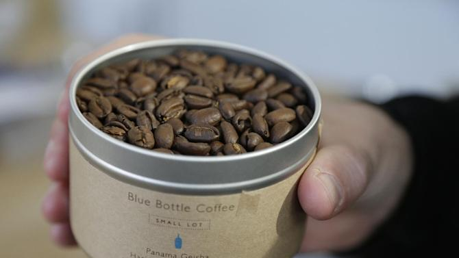 In this photo taken Thursday, Jan. 3, 2013, James Freeman, founder of Blue Bottle Coffee holds a container of Panama Geisha coffee beans  at his roastery in Oakland, Calif. (AP Photo/Eric Risberg)