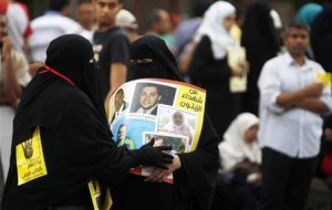 A member of the Muslim Brotherhood passes a poster…