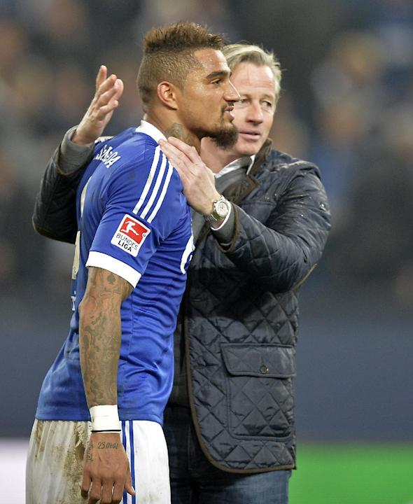 Schalke's Kevin-Prince Boateng, left, is embraced by Schalke head coach Jens Keller after the German  Bundesliga soccer  match between FC Schalke 04 and Werder Bremen in Gelsenkirchen, Germany, Saturd