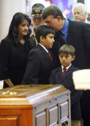 In this photo shot by a pool photographer and later vetted and approved for release by the Green family, John Green, top right, kisses his son Dallas on the head as the family follows the casket of daughter and sister Christina Green, at her funeral mass in Tucson, Ariz. Wednesday, Jan. 13, 2011. At left is mother Roxanna and right is Camden Grant, Christina's godmother's son. Christina Green was the youngest gunned down in last Saturday's shooting rampage in Tucson. (AP Photo/Rick Wilking, Pool)