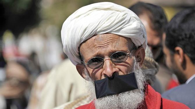 ARH107. Sanaa (Yemen), 22/11/2014.- A Yemeni protester has his mouth tapped during a rally against the Shiite insurgency, in Sana'a, Yemen, 22 November 2014. Since September, the Shiite Houthi rebels have spread throughout Yemen, using armed members to gain control of large parts of the country, including the capital Sanaía. Houthi fighters have occupied government buildings and military installations, amid an almost total absence of resistance from the security forces. (Protestas) EFE/EPA/YAHYA ARHAB